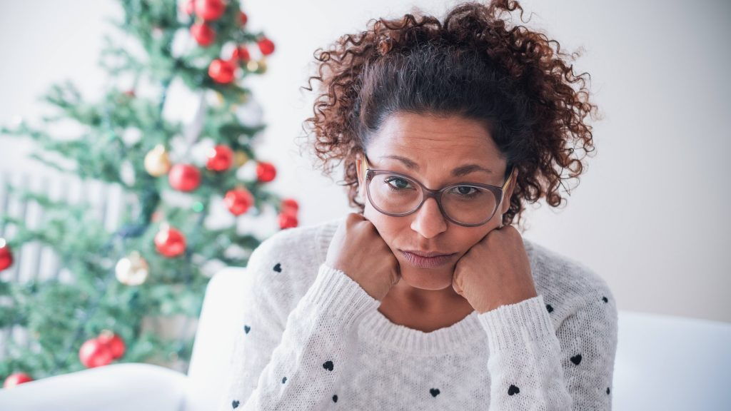a young African American woman in a white sweater, wearing glasses, looking sad, disappointed, stressed and tired with her head resting on her hands and a holiday Christmas tree and decorations in the background