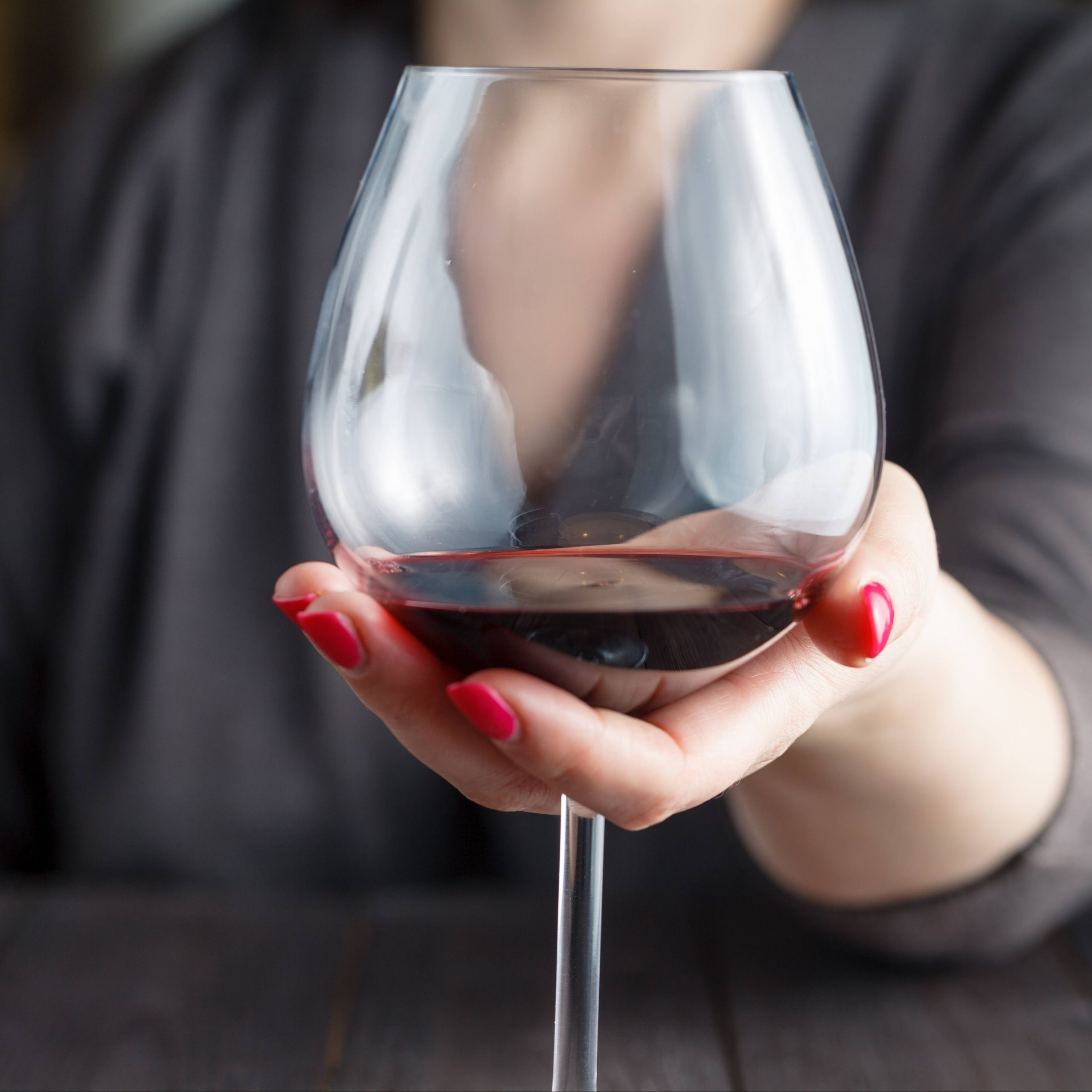 a Caucasian woman in a grey sweater sitting at a table, wearing red fingernail polish and holding a glass of red wine