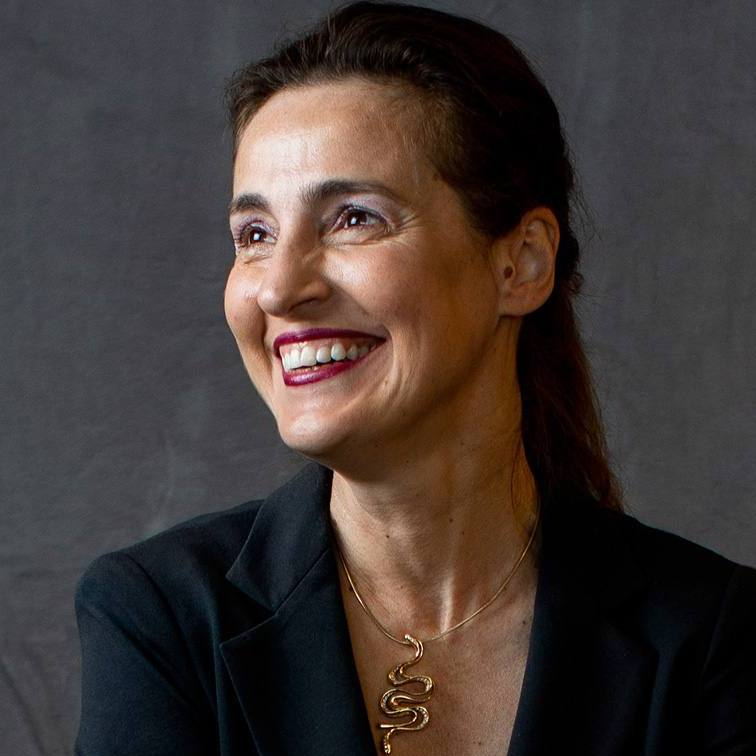 an environmental bio picture with a gray background of Dr. Evanthia Galanis in a dark suit wearing a gold necklace and smiling