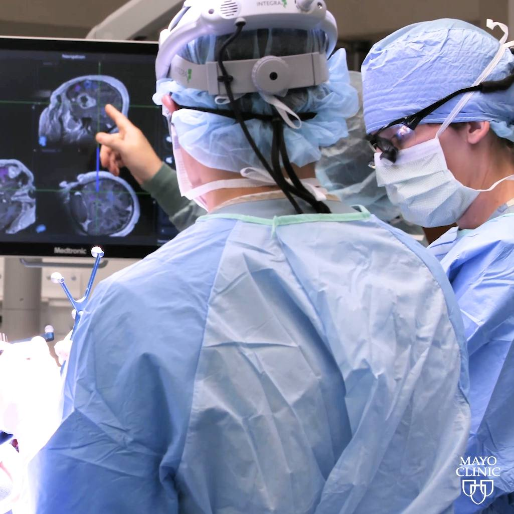 brain tumor surgery with surgeon's in the operating room looking a radiology Xray images of a person's head