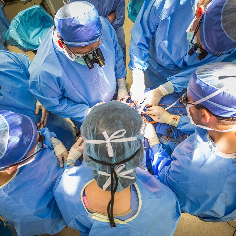 surgeons in blue surgical gowns performing a transplant