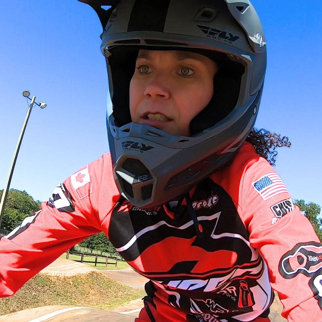 brain tumor patient Melissa Whiley wearing a helmet and racing her motocross bike outside with a blue sky