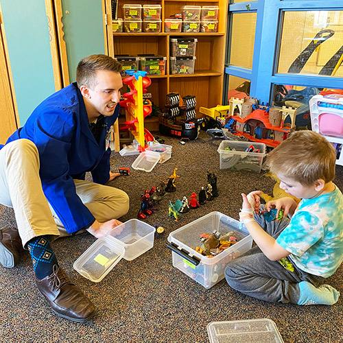 medical researcher Merrick Ducharme sitting on the floor in the Children's Center playroom with a pediatric patient playing with toys