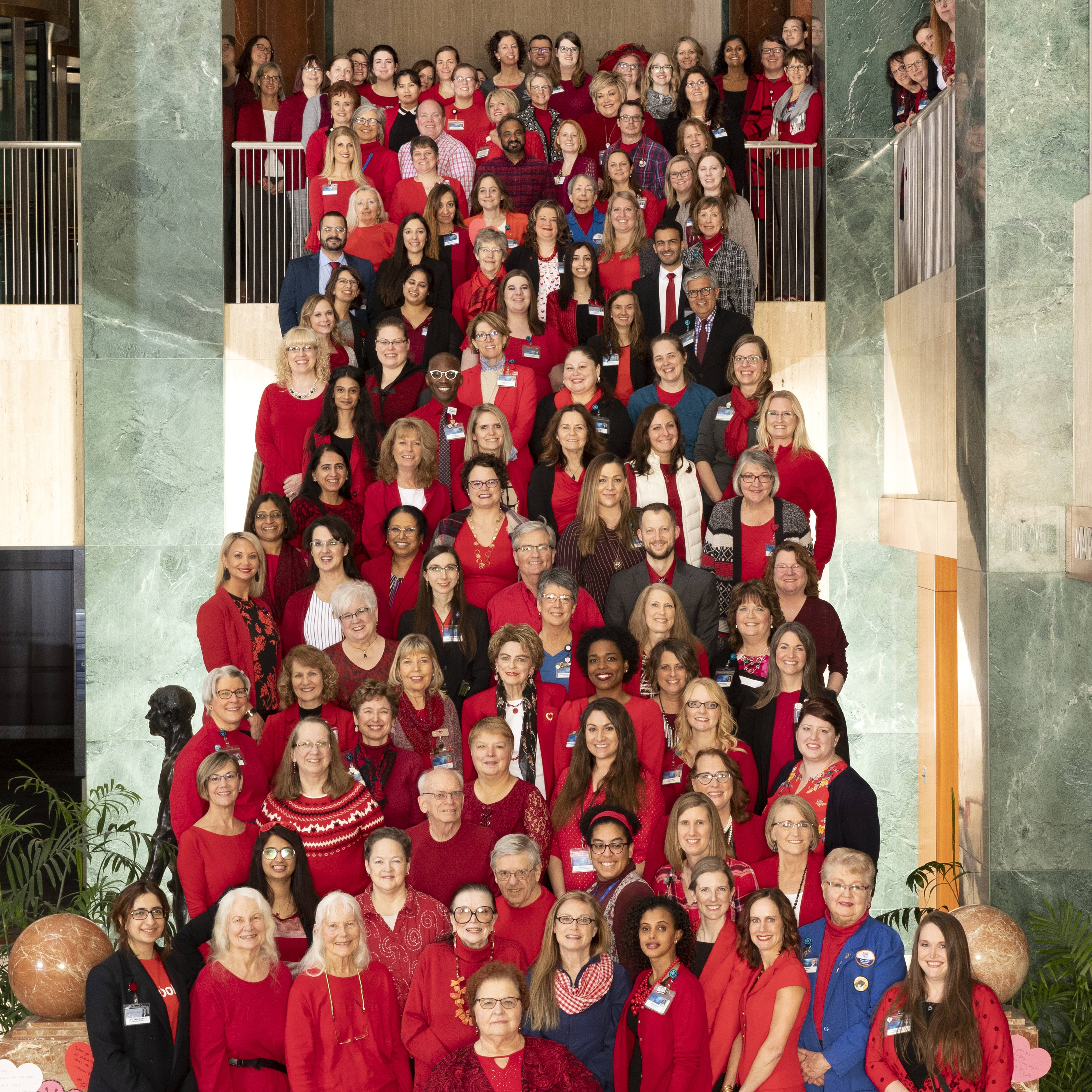 Employees at Mayo Clinic in Rochester line a stairway dressed in red.