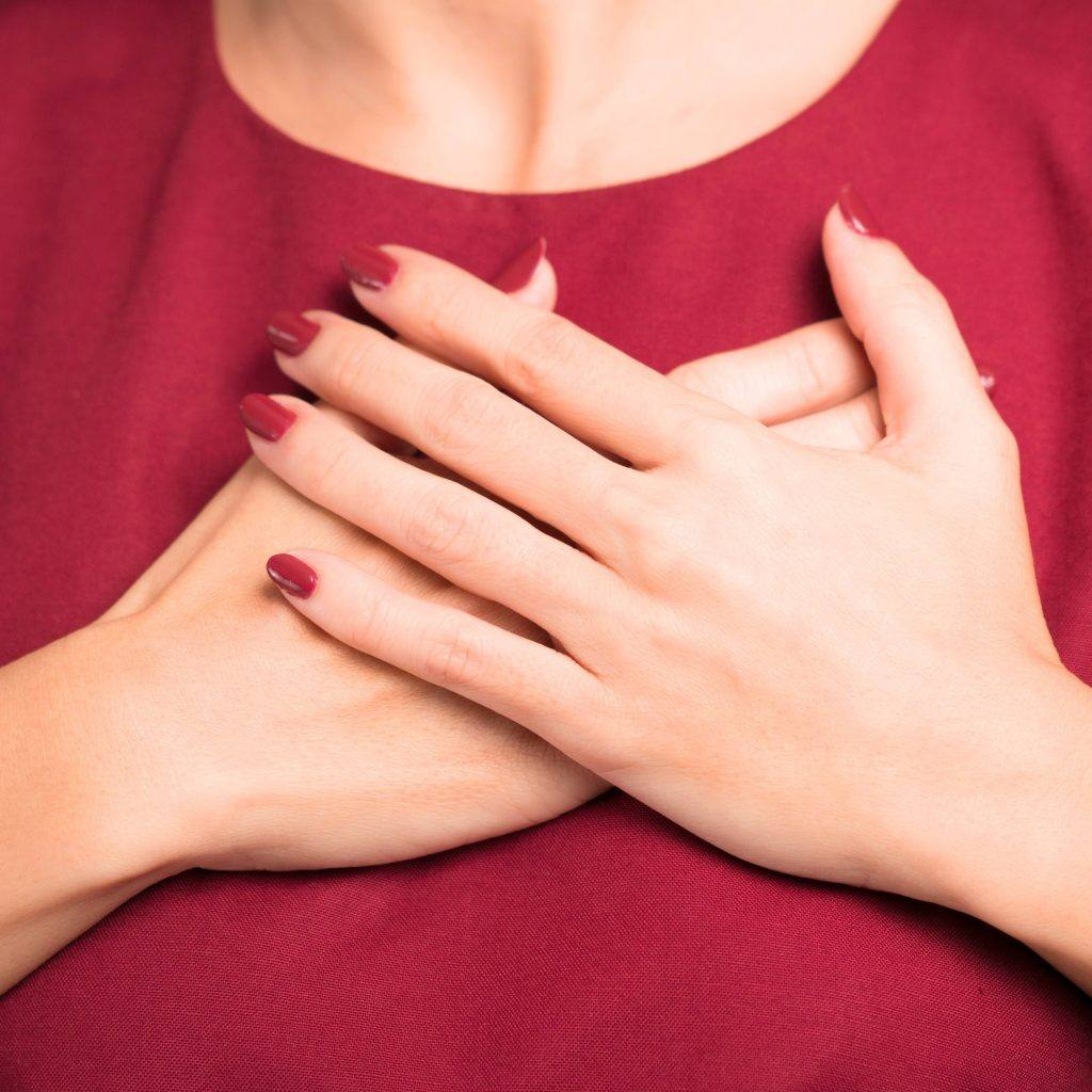 a white woman in a red top with red nail polish holding her across her chest near her heart