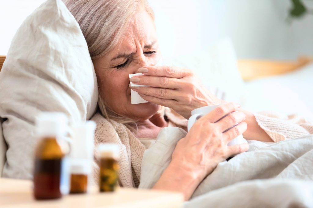 an older or middle-aged white woman sick in bed, with a cold or flu, holding a tissue sneezing and coughing