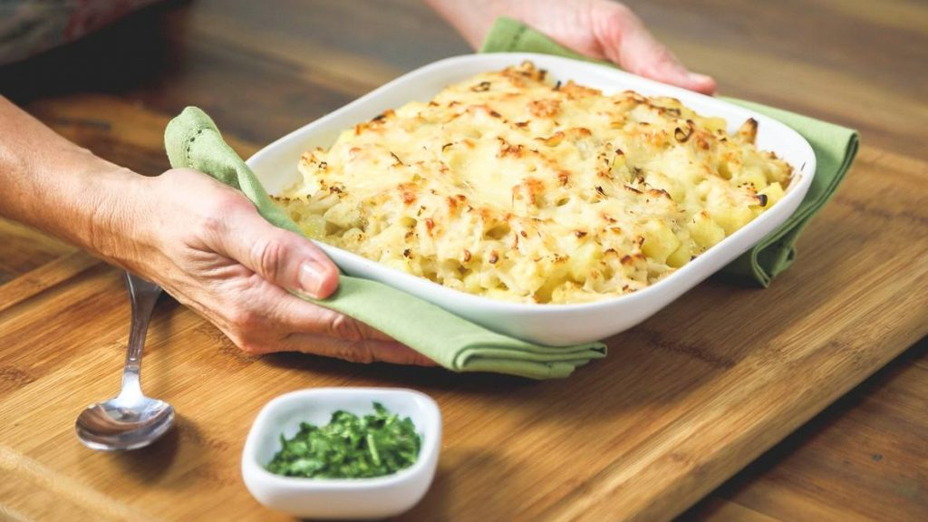 a person serving potato cauliflower au gratin in a white dish and holding the casserole dish with green napkins