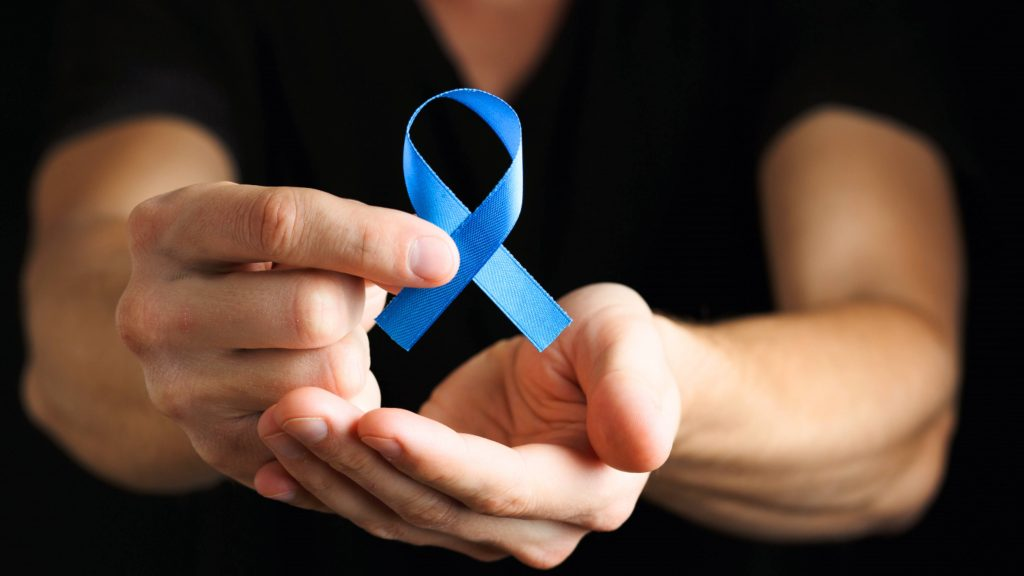 a white man in a dark shirt with a dark background holding a blue ribbon with his finger tips, representing colon cancer awareness