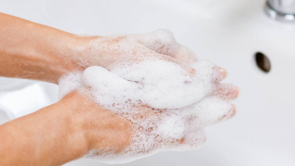 Una persona se lava las manos con agua y jabón en un lavabo