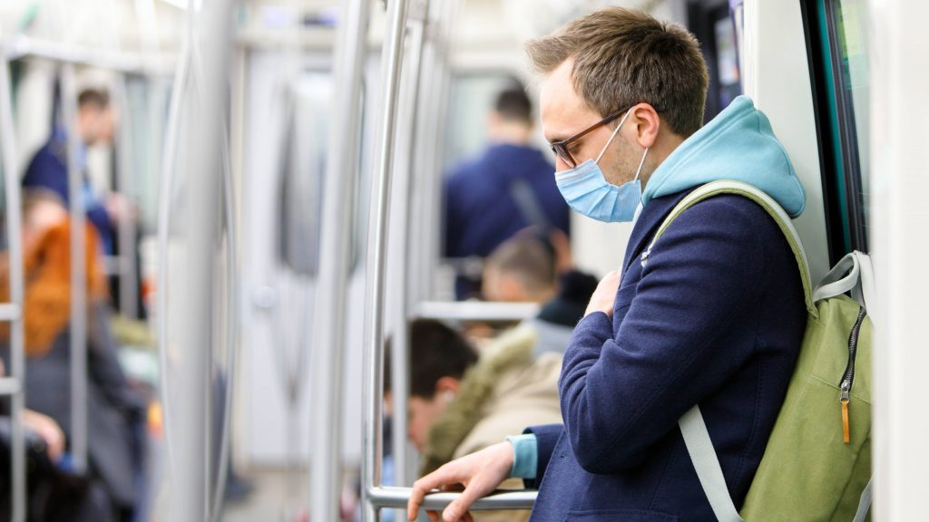 a young white man wearing glasses and carrying a backpack on a subway train, looking sick or ill and wearing a face mask to limit transfer of germs and infectious diseases