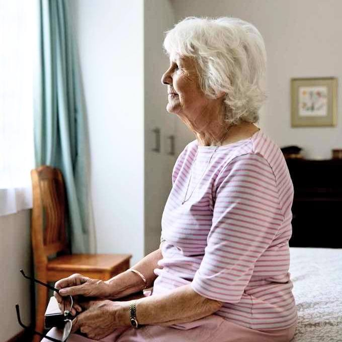 an older white woman with gray hair sitting alone on a bed, looking out a window and thinking