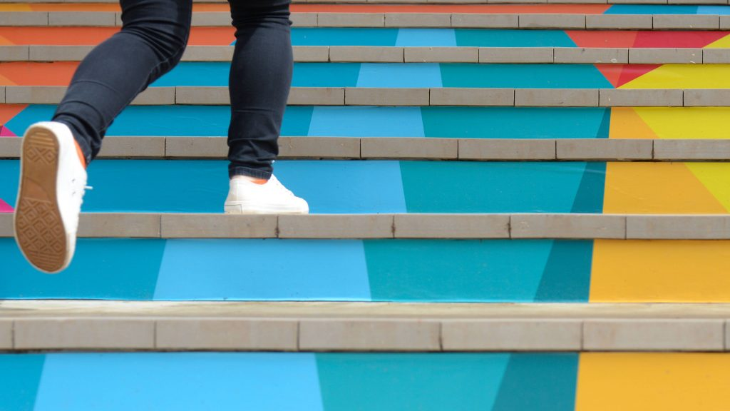 a close-up of a person's lower legs and feet walking up a colorful set of stairs