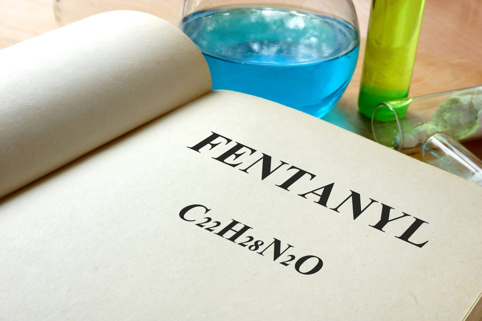 book open to page with fentanyl printed on it, test tubes next to the book