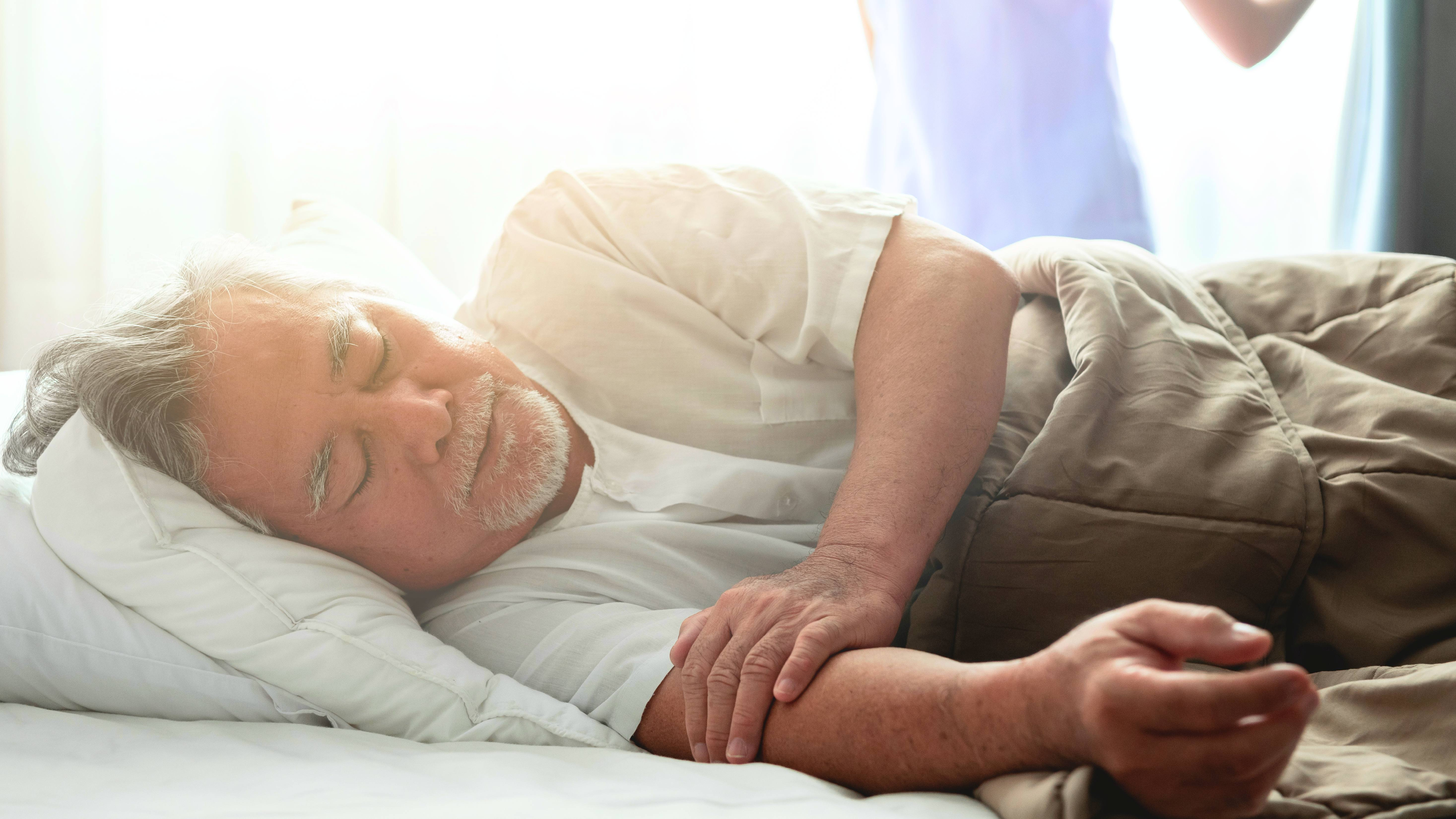 an elderly Asian or Latino man with a beard resting, sleeping under a blanket in bed, perhaps sick with a caregiver in the background opening a curtain