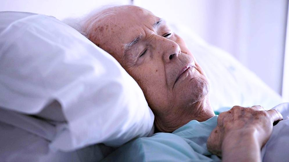 older, aging man in bed, sick, sleeping or dying
