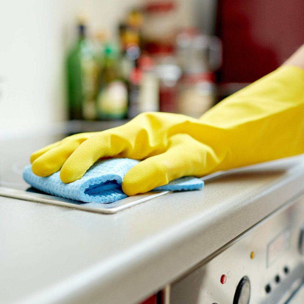 a person wearing a yellow rubber cleaning glove and wiping a stove top with a blue sponge