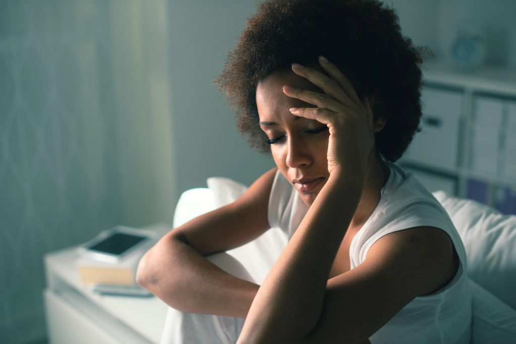 a young African American woman trying to sleep and sitting in bed in a dark room, with her eyes closed holding her hand on her forehead, perhaps suffering from insomnia, sadness, depression, worry. anxiety, stress