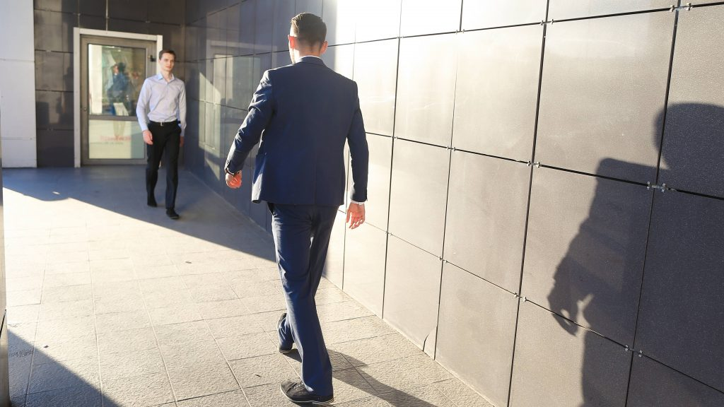 two Caucasian men in business clothes outside in the sunshine walking toward each other, keeping a distance between them