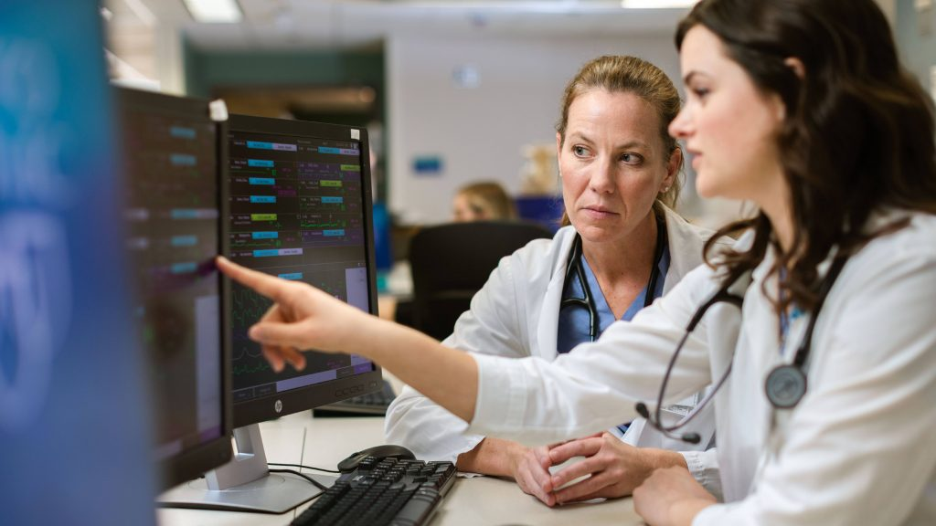 two Caucasian women in white lab coats, perhaps researchers, reviewing medical and scientific data on a computer screen