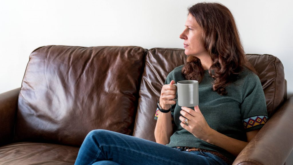a middle-aged Caucasian woman in jeans sitting on a brown couch, holding a coffee mug, looking thoughtfully and seriously out a window, seeming calm