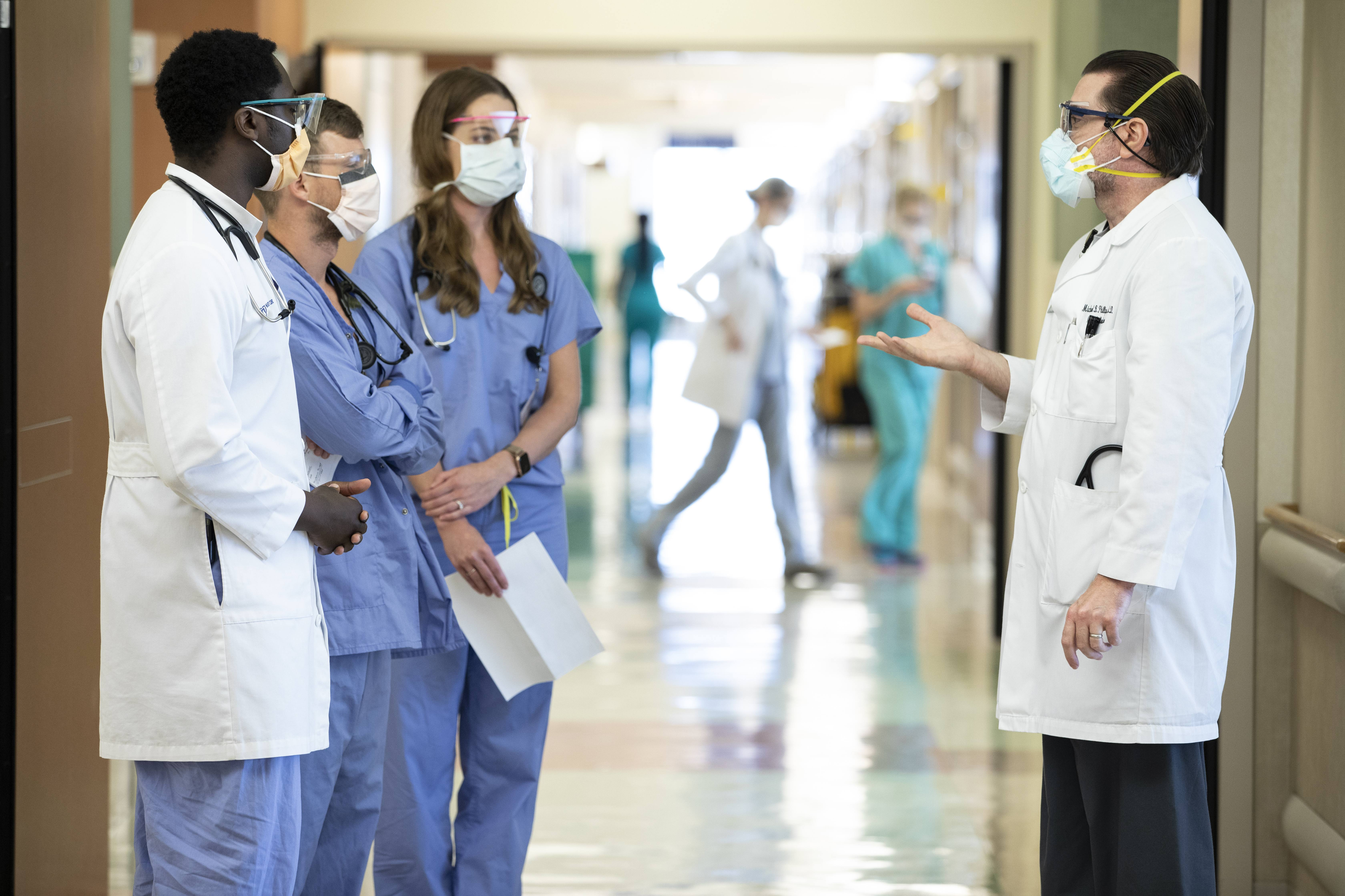 Mayo Clinic medical personnel in scrubs, white jackets and protective face masks in a hospital corridor having a conversation. 2 in blue scrubs, 2 in white coats, other staff passing in background.