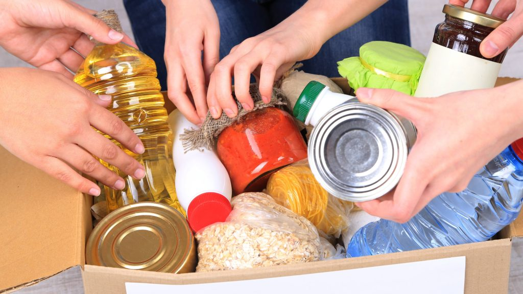 a box of donated foods and essential items needed in an emergency, with the hands of people placing items in the box