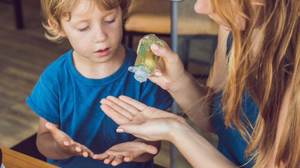 a white adult woman, perhaps a mother, putting hand sanitzer on her hand to help a little white boy, sitting next to her, with his hands out