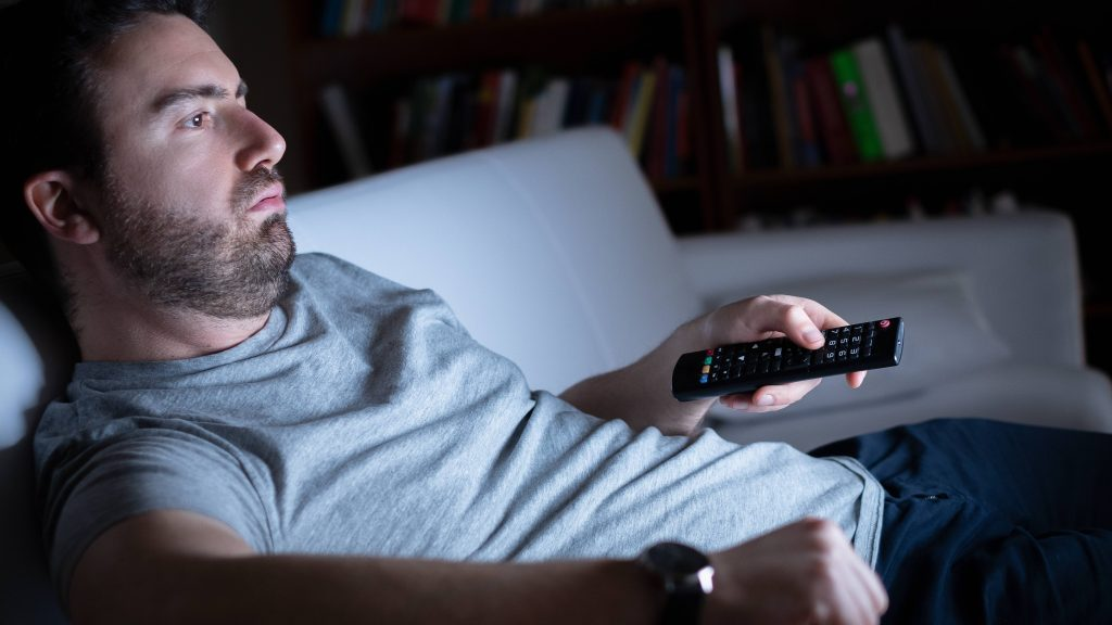 a white man in a jeans and a gray t-shirt slouched on a couch, holding a tv remote and watching television in the dark