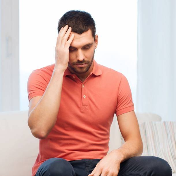 a white man in an orange shirt sitting on a couch, touching his forehead and looking sick, sad, maybe with a headache