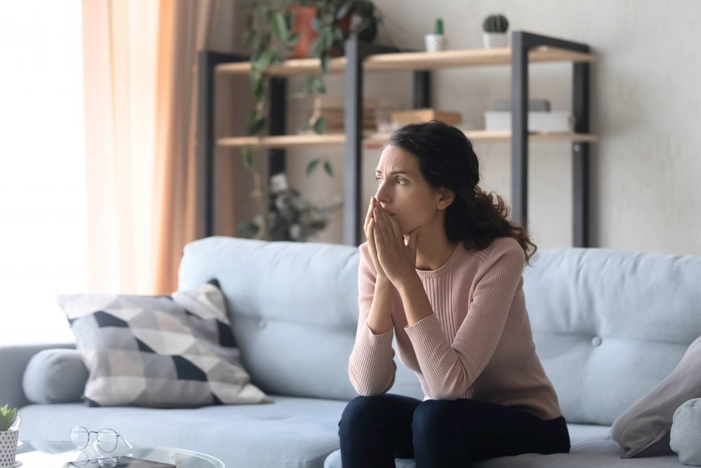a white woman sitting on a couch looking out a window, crossing her hands and looking sad, worried, concerned