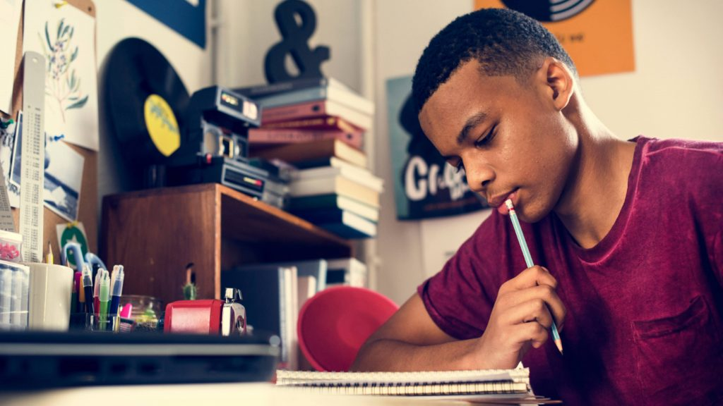 a young Black teenage boy in a t-shirt working at a desk, with a notebook and a pencil, perhaps doing homework in his bedroom or college dorm room
