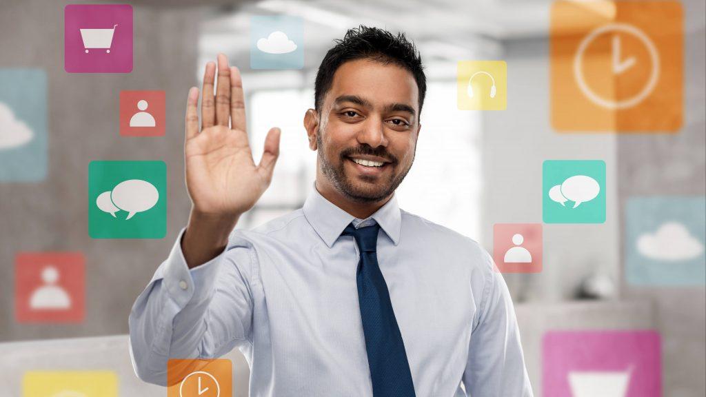 Un joven empresario con corbata en una oficina y sonriendo, rodeado de iconos gráficos comerciales