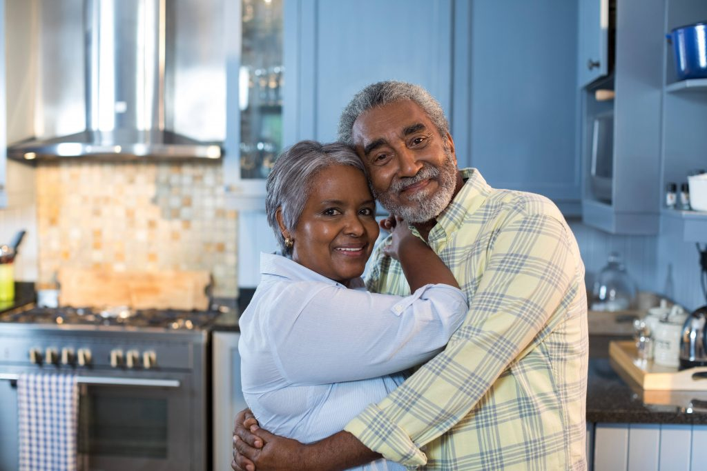 a middle-aged couple, perhaps Black or Latino with little brown skin tones, smiling, happy and hugging in a kitchen