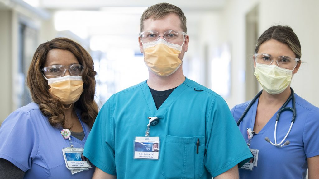 three Mayo Clinic employees in medical scrubs wearing face masks and eye coverings