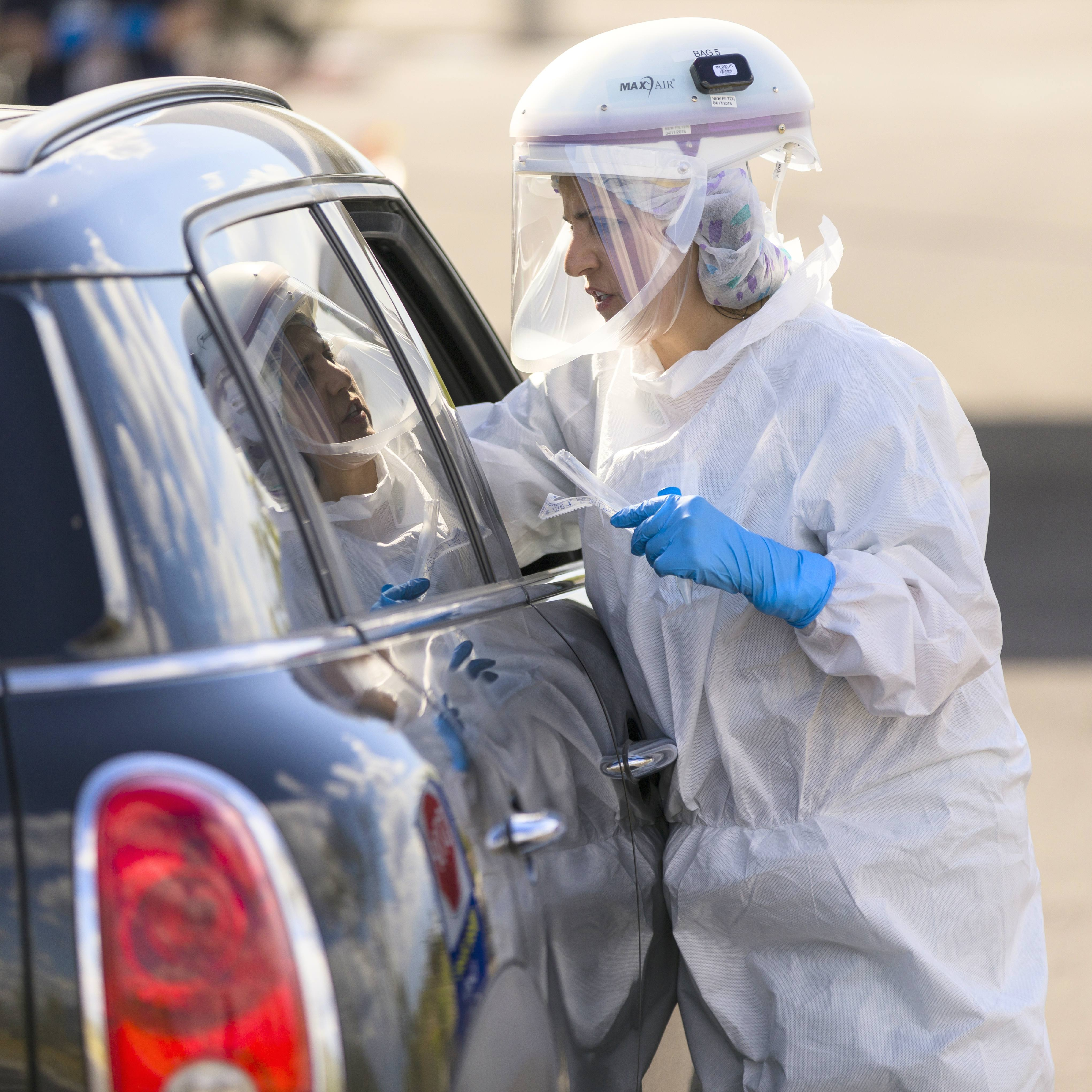 a Mayo Clinic medical staff person in Personal Protective Equipment, PPE, testing patients for COVID-19 who are in a car at a drive-up testing site