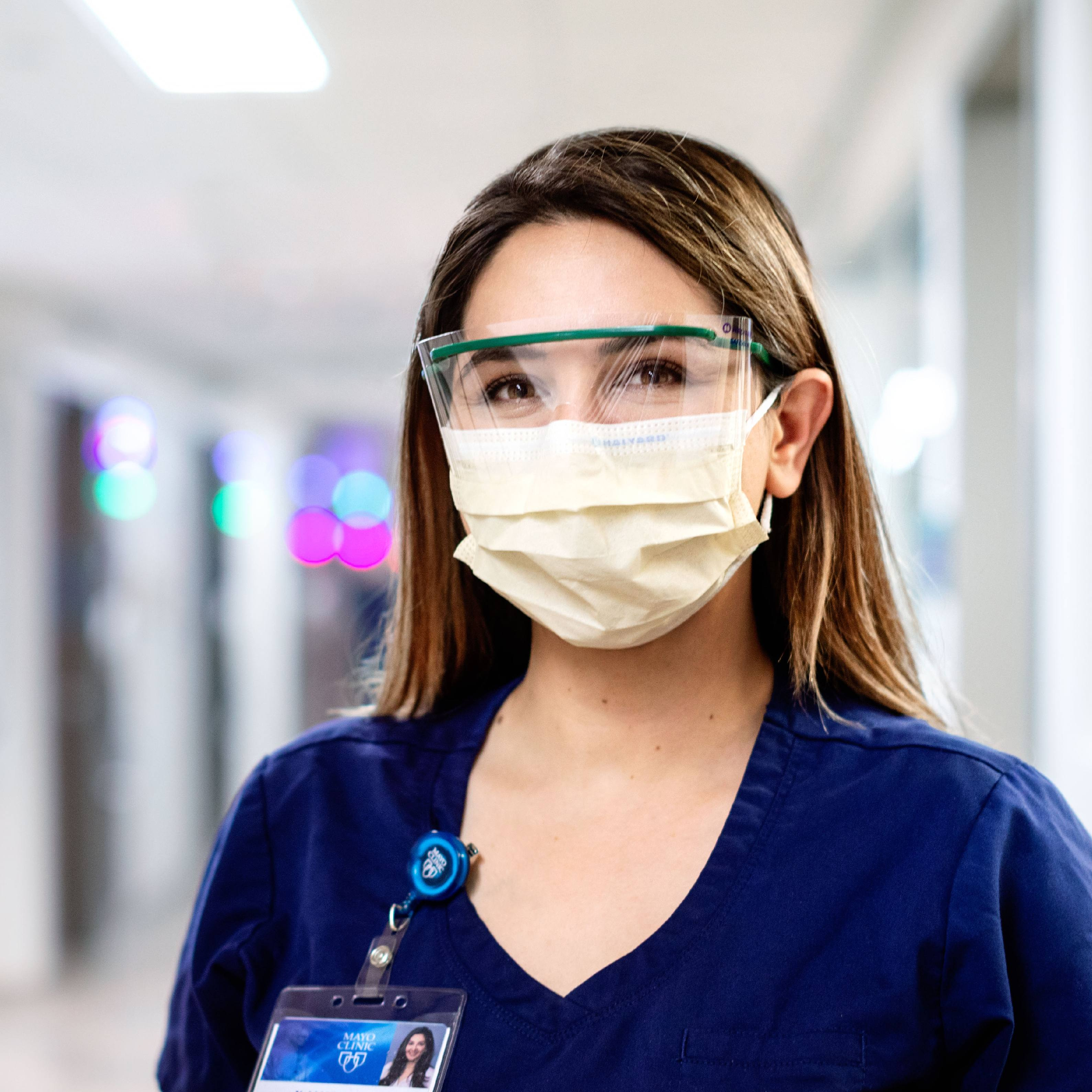 a white or Latino woman in Mayo Clinic medical blue scrubs and wearing eye protection and a face mask in the hospital corridor
