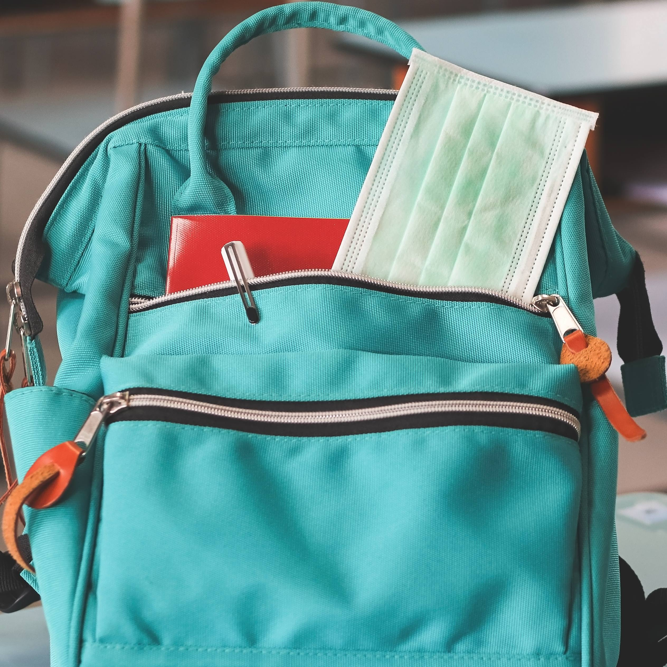 School backpack with mask tucked into pocket and hand sanitizer on desk