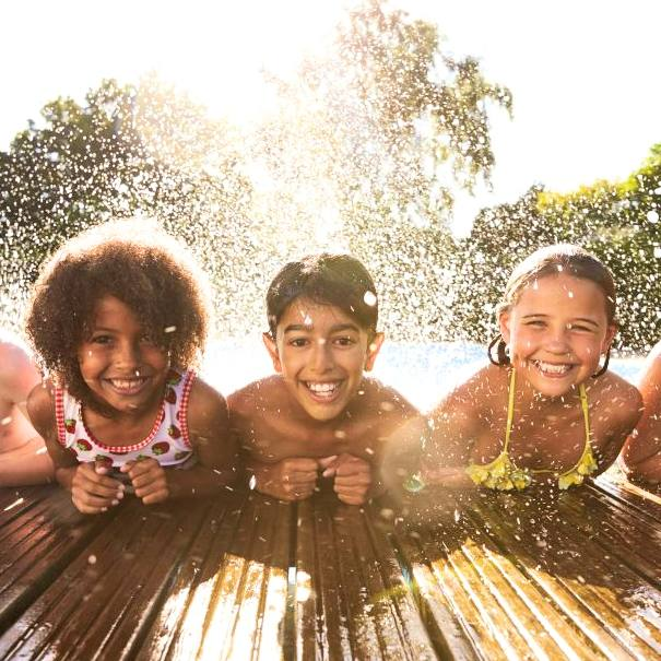 five smiling tweenage girls and boys leaning on the edge of a swimming pool with water splashing behind them