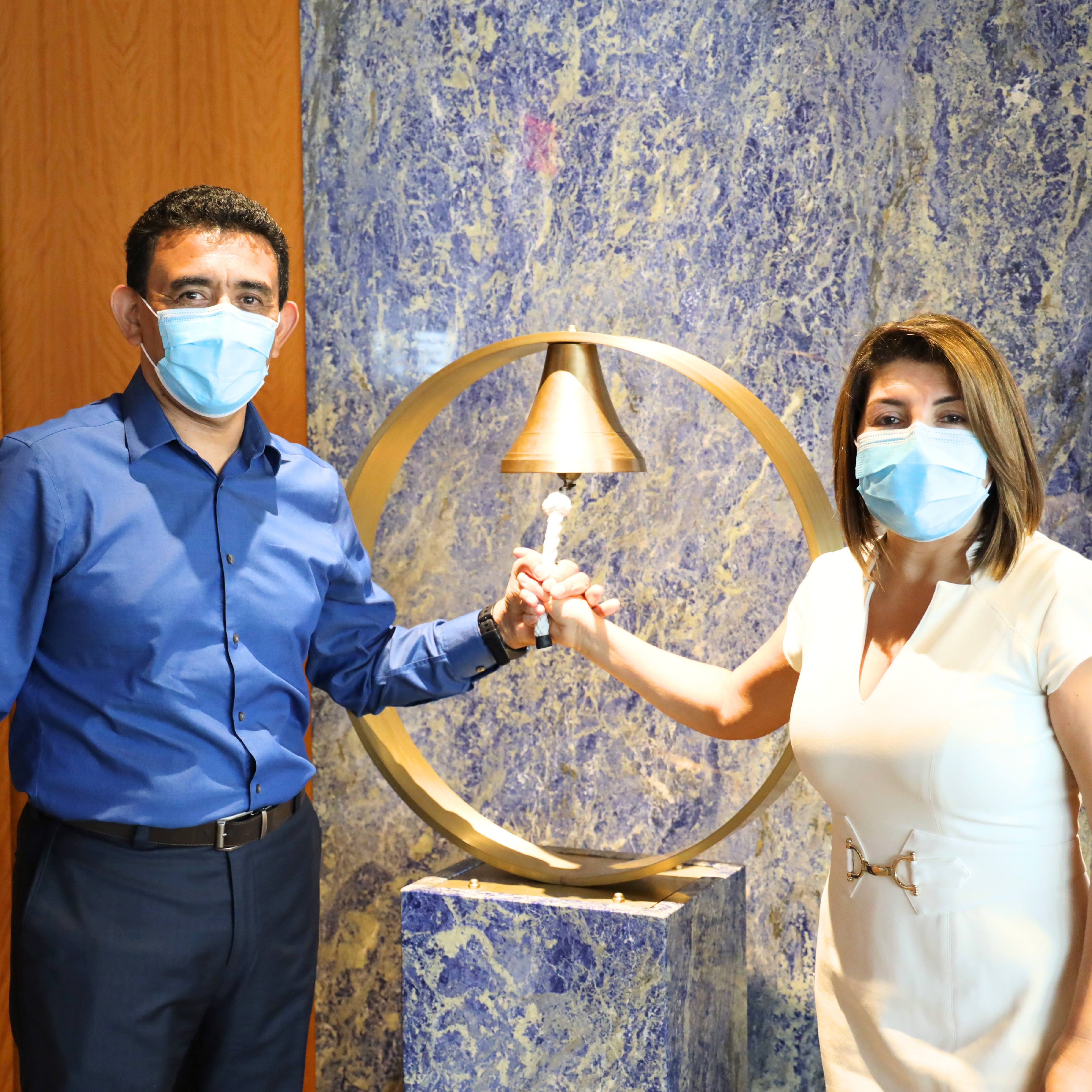 Mayo Clinic Florida cancer patient Eduardo Aguero with his family after final chemo treatment, all wearing protective facemasks, while he rings the bell because his treatment is completed