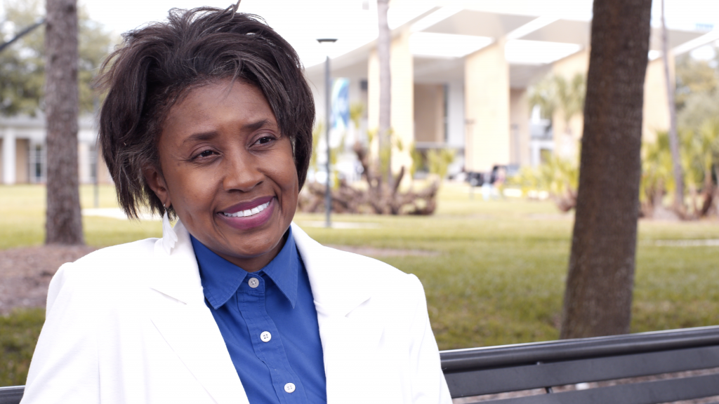 Mayo Clinic Florida eye sight patient Sandra Blue outside in a blue blouse, white jacket and smiling