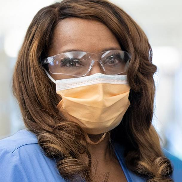 a Black woman in blue medical scrubs, wearing personal protective equipment PPE eye goggles and a face mask