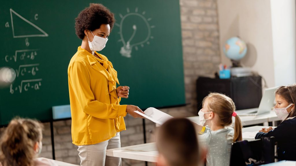 a Black woman teacher wearing a mask and standing in front of a classroom of students wearing face masks, with a chalkboard in the background