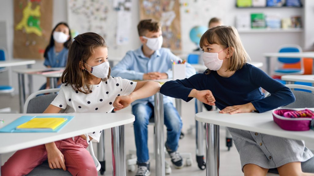 a classroom of elementary or middle-school aged children wearing masks and praticing social distancing, touching elbows