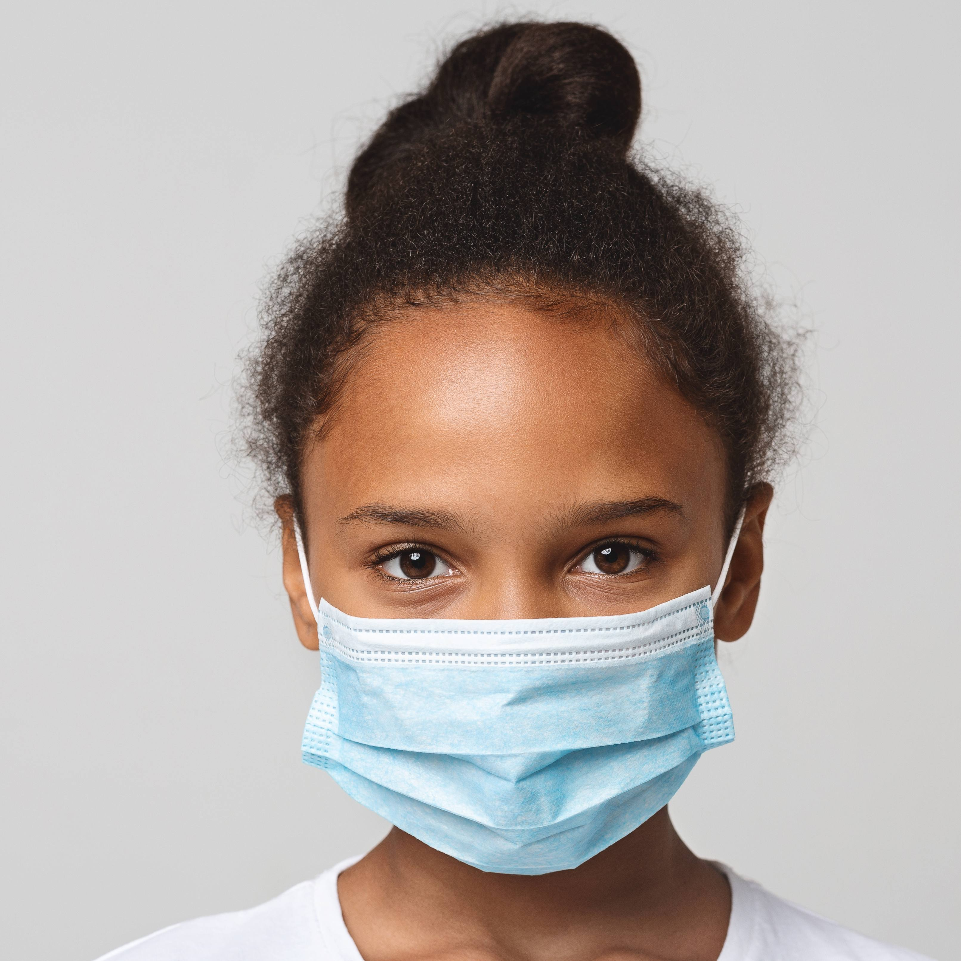 a little Black school-aged girl with a plain white background and wearing a face mask