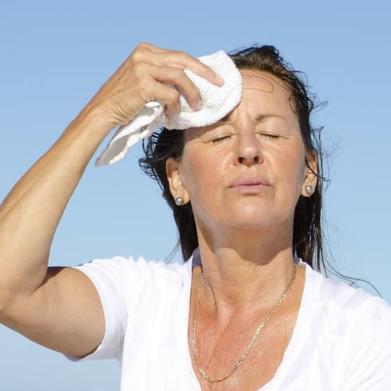 a middle aged white woman outside facing the sun with her eyes closed looking tired and hot, wiping sweat from her forehead, perhaps after exercising