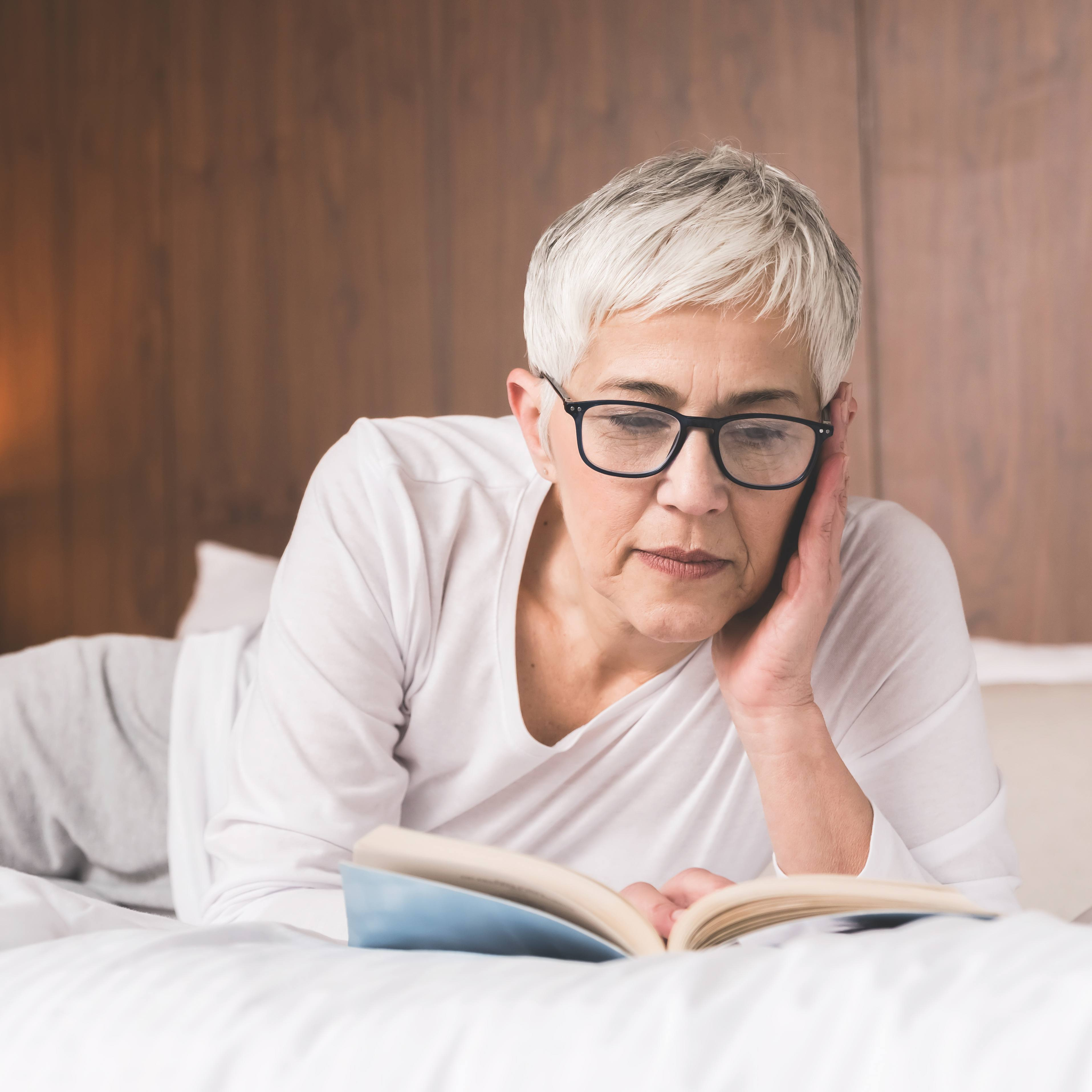a white middle aged woman with light gray hair, wearing glasses and resting, relaxing a bed reading a book
