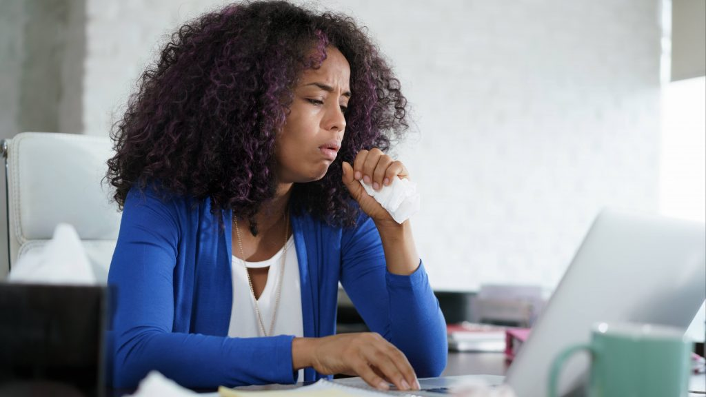 a young Black woman looking sick or ill working at a computer on a table and holding a tissue to her face as she coughs or sneezes