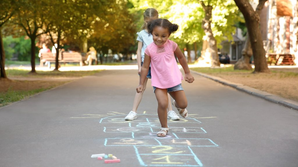 two little girls, one Black and one caucasian, playing hopscotch outside in a park with trees on a sunny day