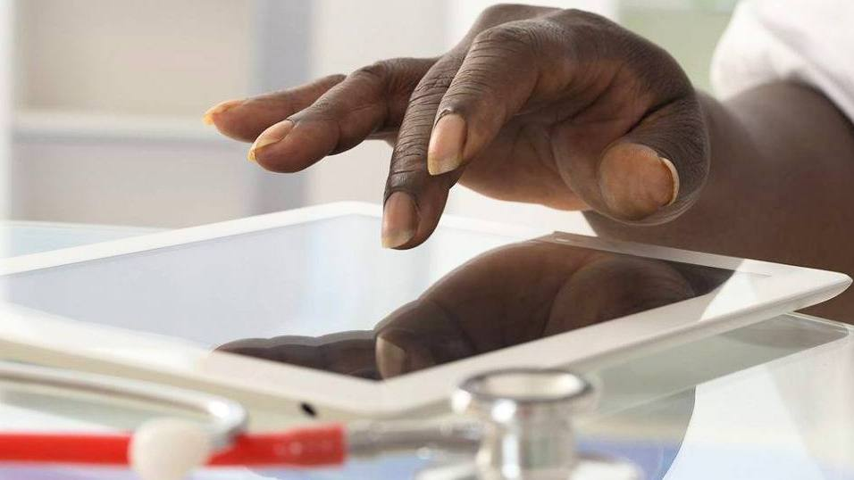 closeup of a Black person, perhaps in a medical office, with his or her hand on a iPad tablet with a stethoscope next to it on a table (original)