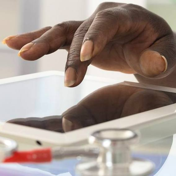 closeup of a Black person, perhaps in a medical office, with his or her hand on a iPad tablet with a stethoscope next to it on a table
